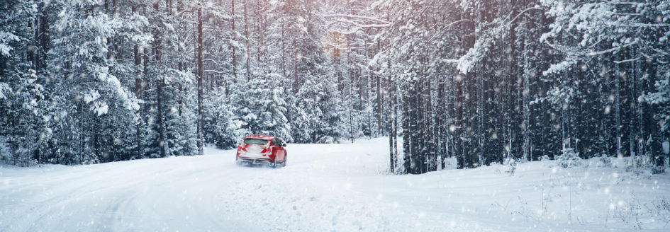 a red car driving through the snow in the winter